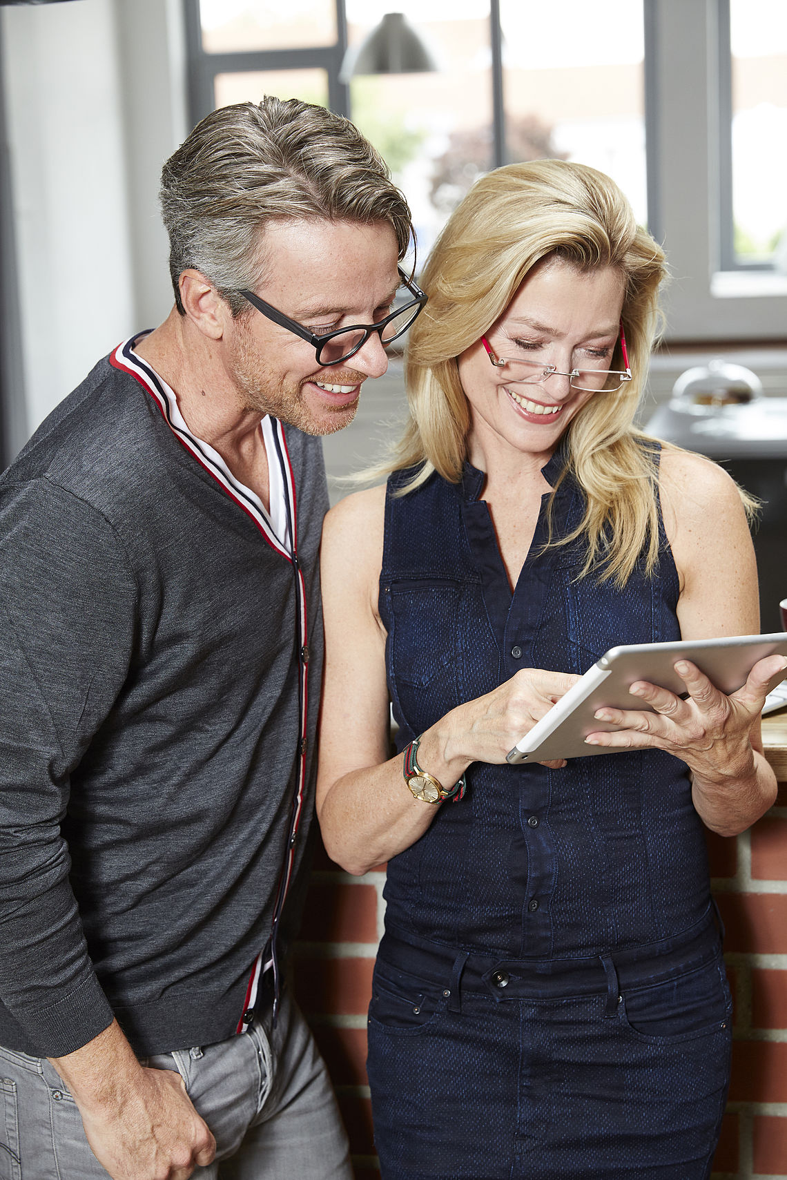 Man and woman with tablet PC in reading glasses