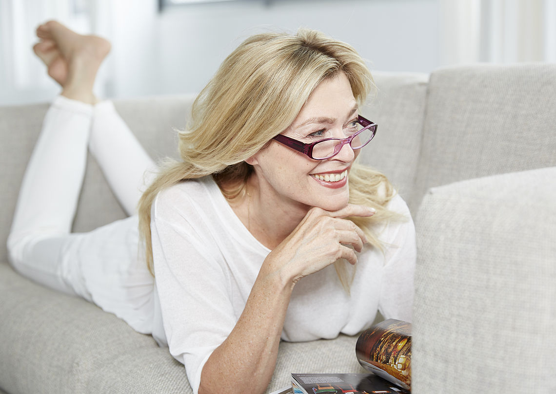 Woman lying on couch, wearing reading glasses Verona
