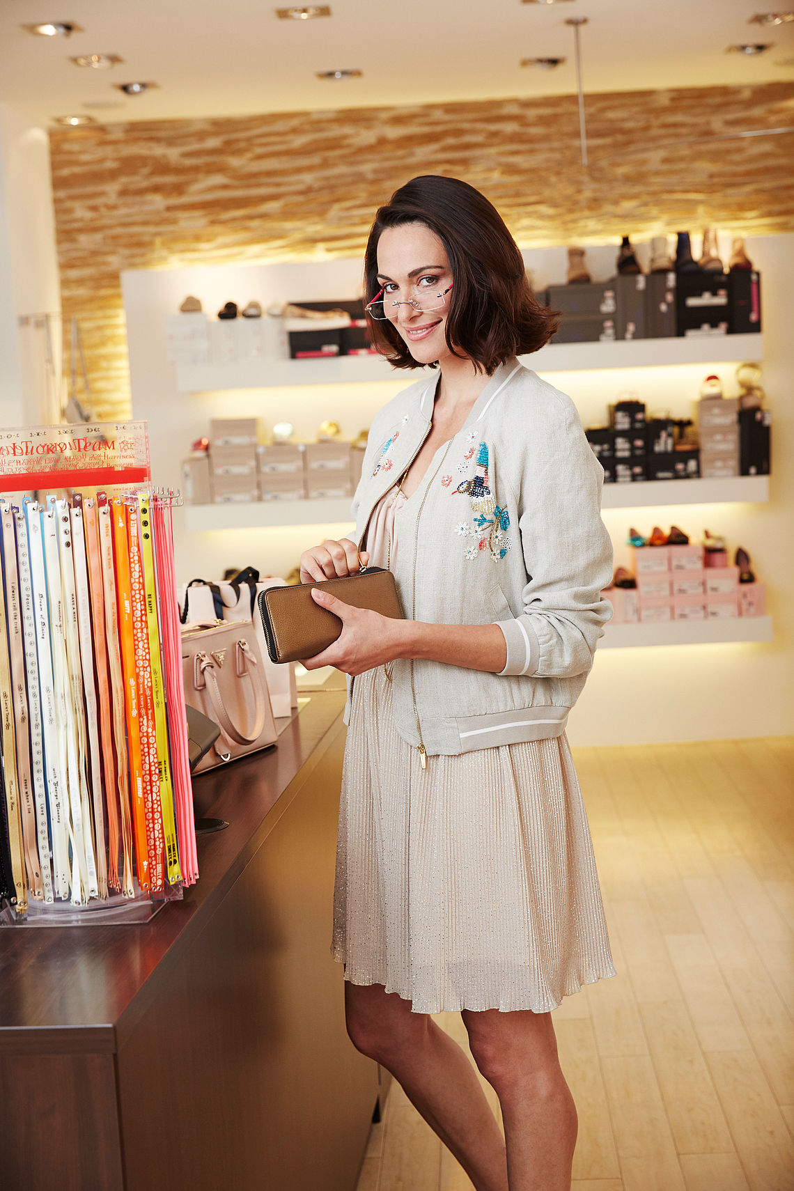 woman in a shop with purse, wearing reading glasses monaco