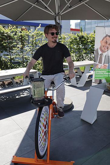 uvex-group-betriebliches-gesundheitsmanagement-mitarbeiter-sitzt-auf-einem-fahrrad-mit-mixer-für-smoothies