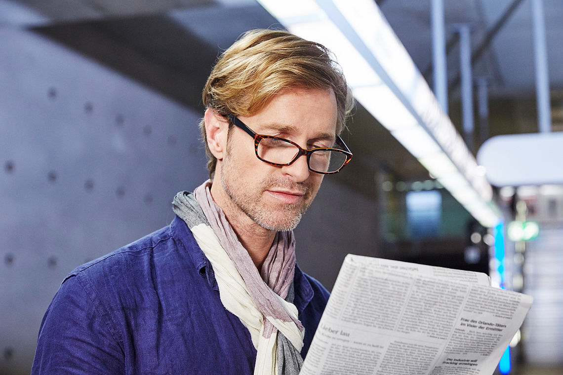 man with newspaper, wearing reading glasses havanna