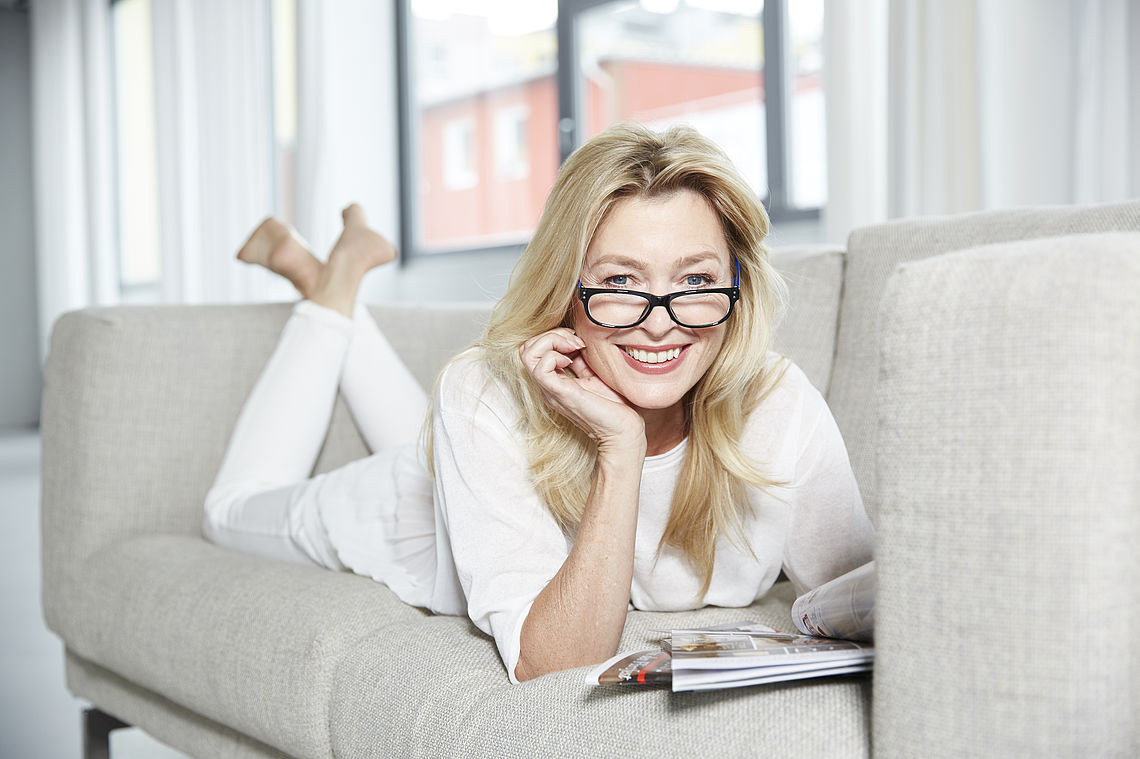 Woman lying on couch, wearing reading glasses San Francisco blue