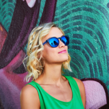 woman in front of wall waering sunglasses
