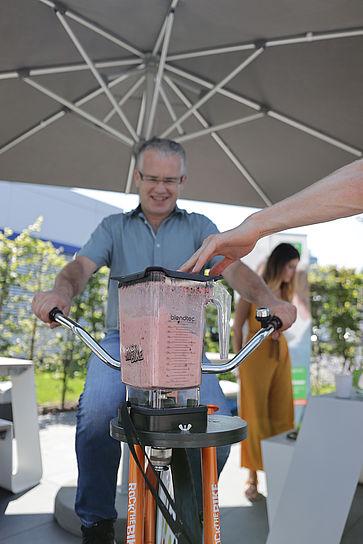 uvex-group-betriebliches-gesundheitsmanagement-mitarbeiter-sitzt-auf-einem-fahrrad-mit-mixer-für-smoothies-und-tritt