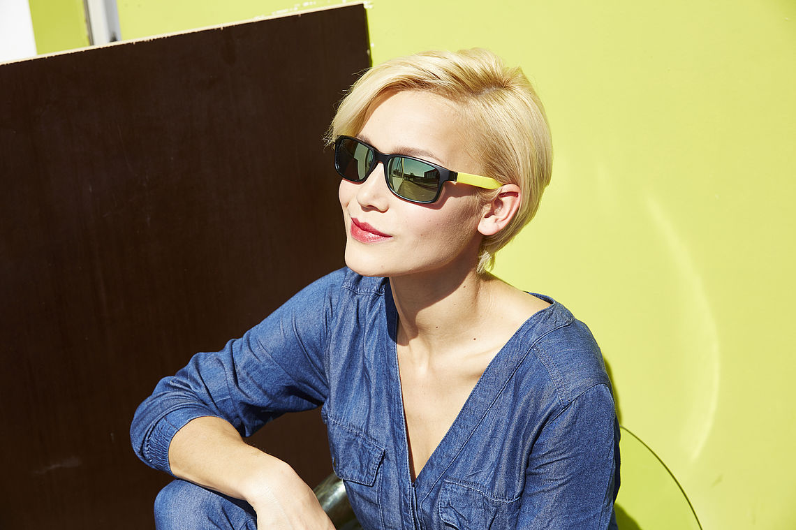 Blonde woman sitting in front a door with sunglasses