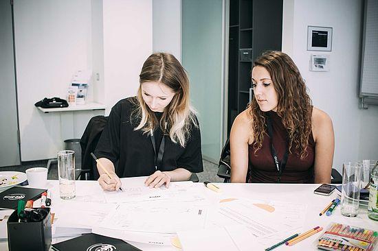 teilnehmerinnen-der-creative-day-challenge-bei-der-uvex-group-am-skizzieren-ihrer-idee