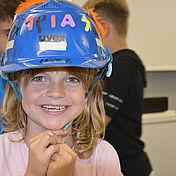kind-mit-uvex-Arbeitsschutzhelm-auf-dem-Kopf