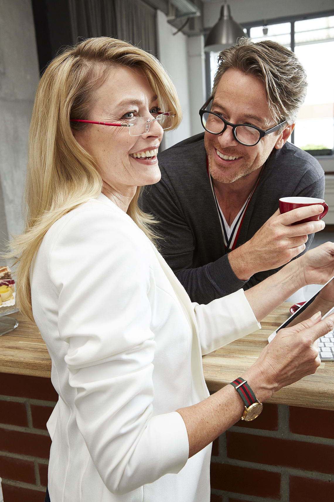 Man and woman drinking coffee, wearing reading glasses