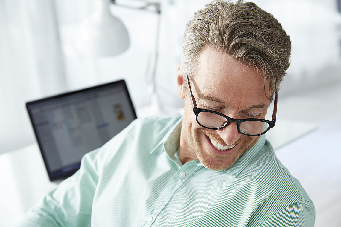 Man in office smiling, wearng reading glasses Amsterdam black / brown