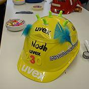 gelber-arbeitsschutzhelm-mit-verzierung-federn-und-buntem-klebeband