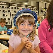 lächelndes-kind-mit-selbst-verzierten-uvex-arbeitsschutzhelm-auf-dem-kopf