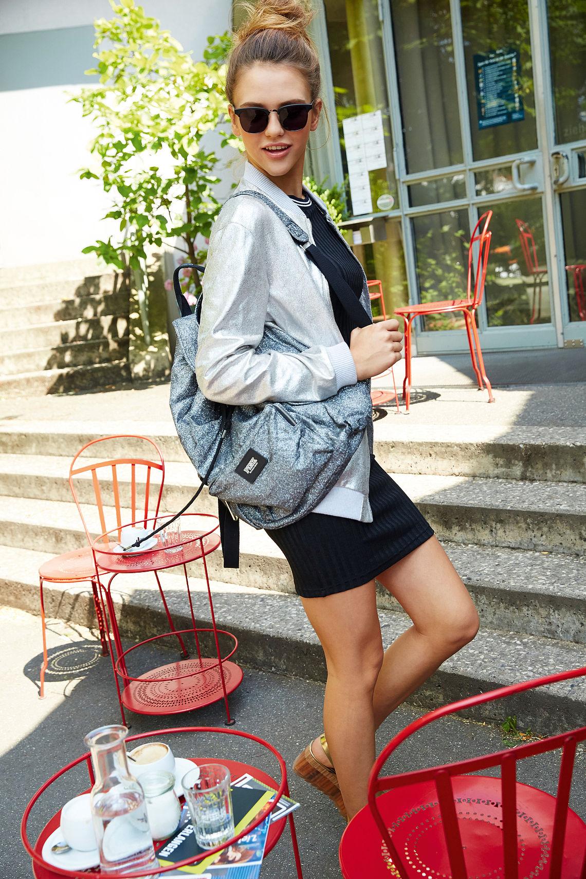 girl with bag, wearing panto sunglasses