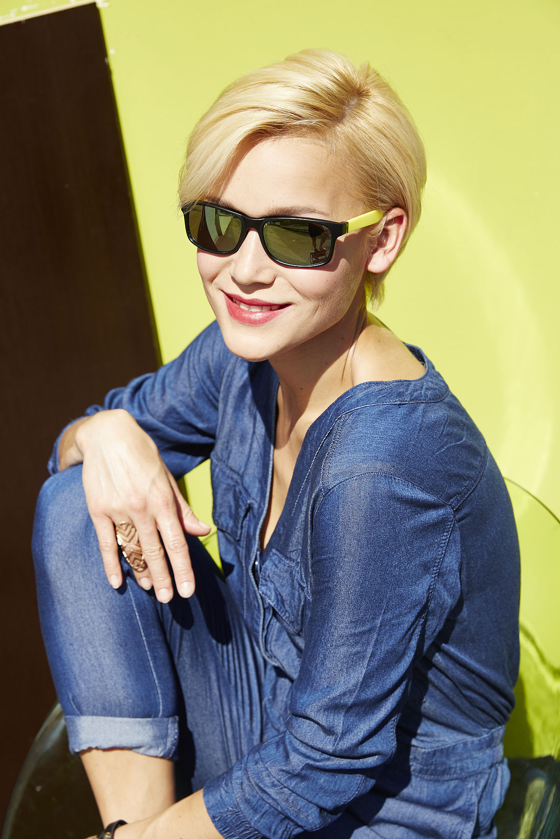 Blonde woman in front the door with sunglasses
