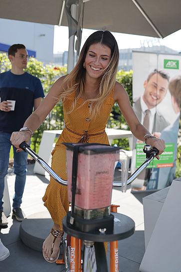 uvex-group-betriebliches-gesundheitsmanagement-mitarbeiterin-sitzt-auf-einem-fahrrad-mit-mixer-für-smoothies