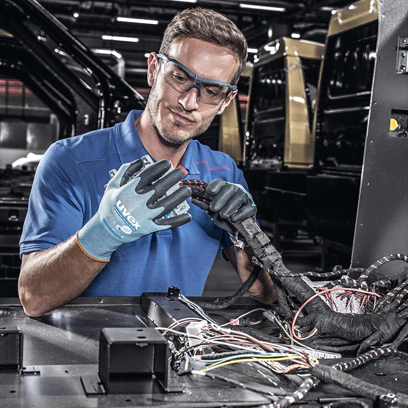 mężczyzna w niebieskich rękawicach ochronnych montuje wiązkę kablową