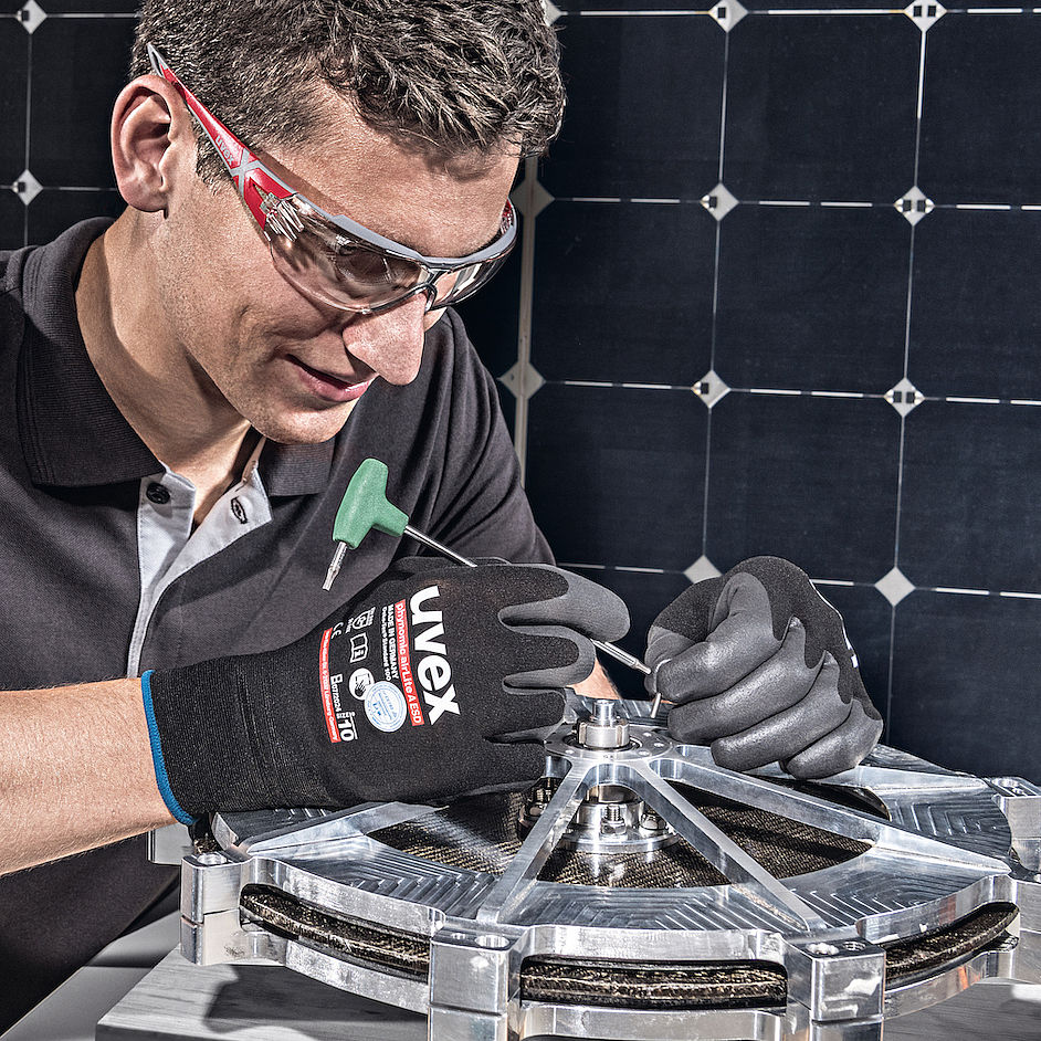 mężczyzna w czarnych rękawiacach ochronnych montuje małe, metalowe elementy