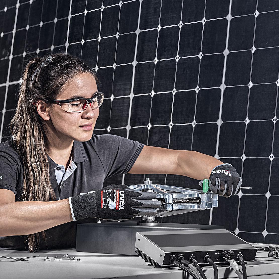 Kobieta w okularach ochronnych i rękawicach uvex wykonuje prace mechaniczne
