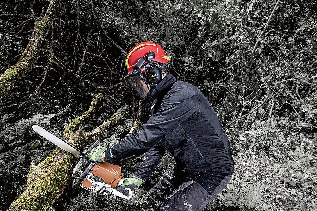 mężczyzna w czeronym kasku dla pilarzy wycina drzewo w lesie