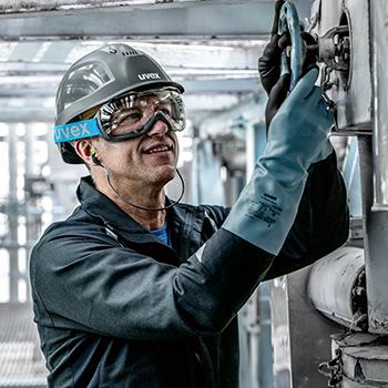 mężczyzna ubrany w rękawice chemiczne, gogle i hełm odkręca duży zawór