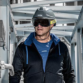 mężczyzna w szarym kasku na głowie i przeciwłonecznych goglach ochronnych patrzy w dal