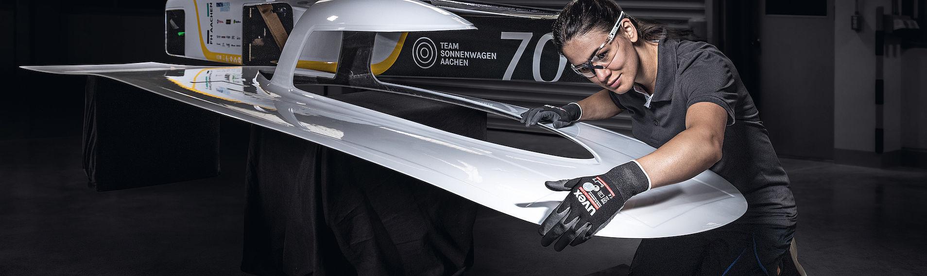 Kobieta w okularach i rękawicach ochronnych kontroluje jakość wykonania powłoki lakierniczej
