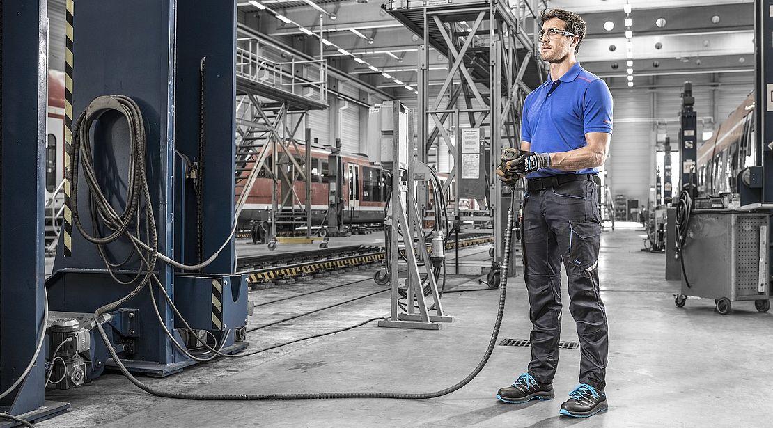 mężczyzna w okularach, odzieży i obuwiu ochronnym obsługuje urządzenie pneumatyczne