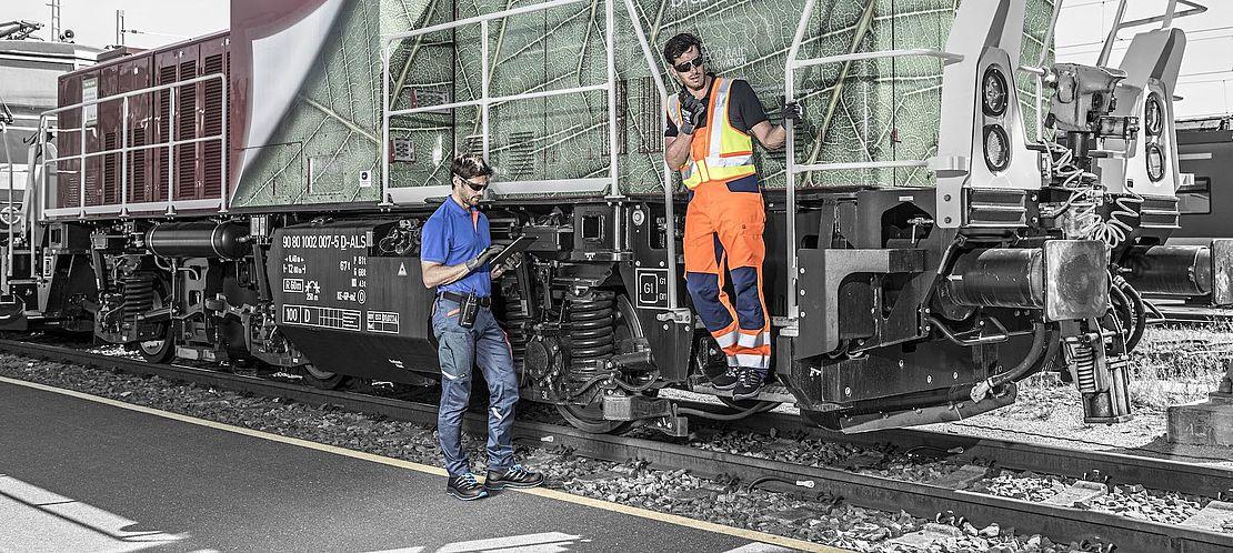 mechanicy w odzieży odblaskowej stoją przy wagonie pociągu