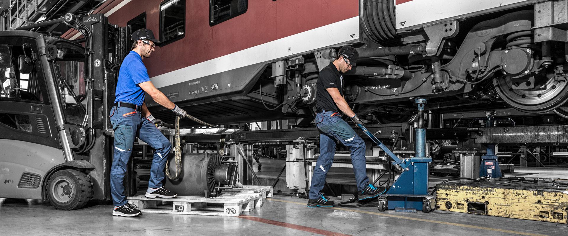 mężczyźni wykonują prace mechainiczne przy wagonie kolejowym